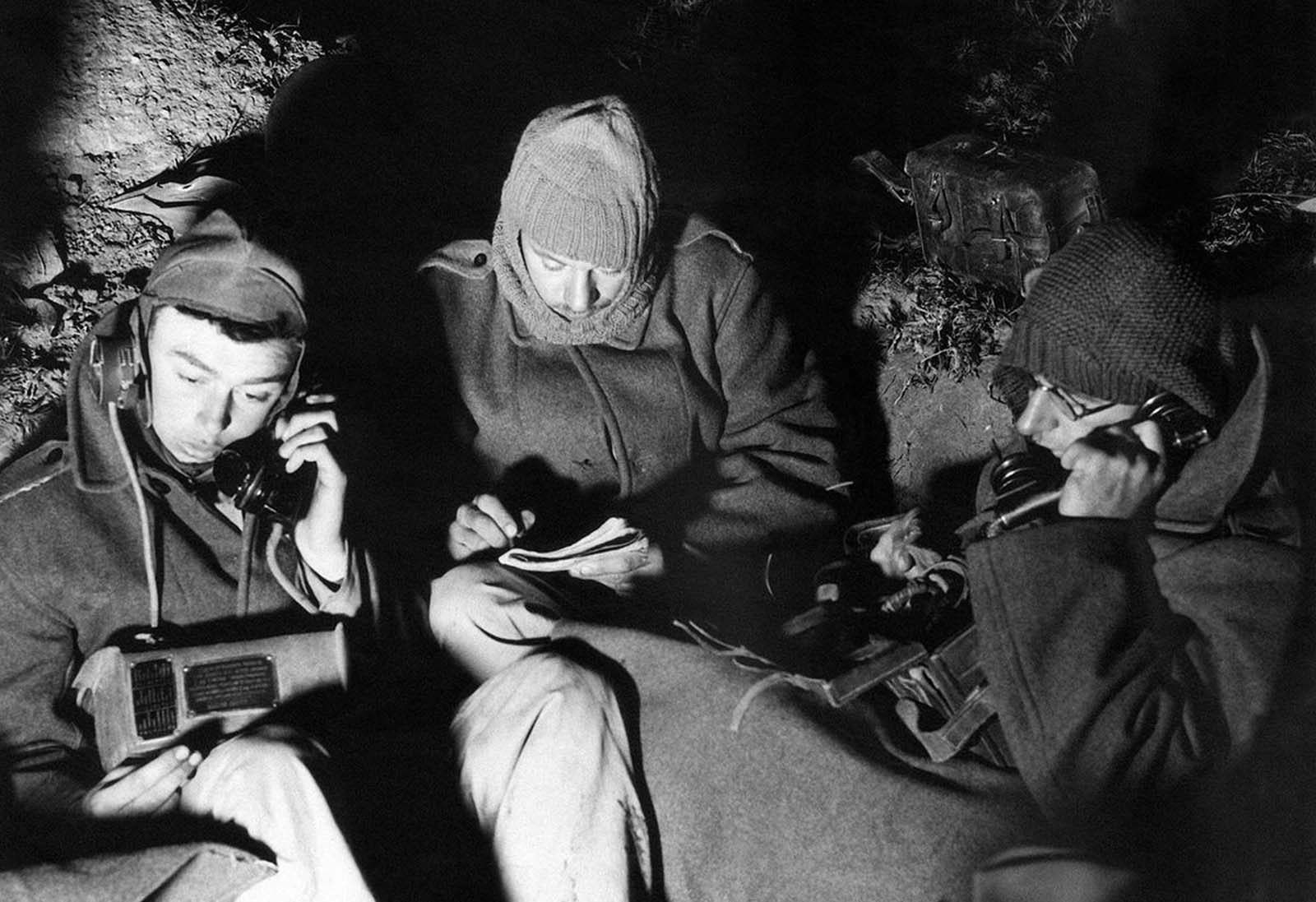 Artillery Signalers at dawn in an outpost in Palestine on December 16. 1940. The men dress warmly to keep out the chill of the desert.