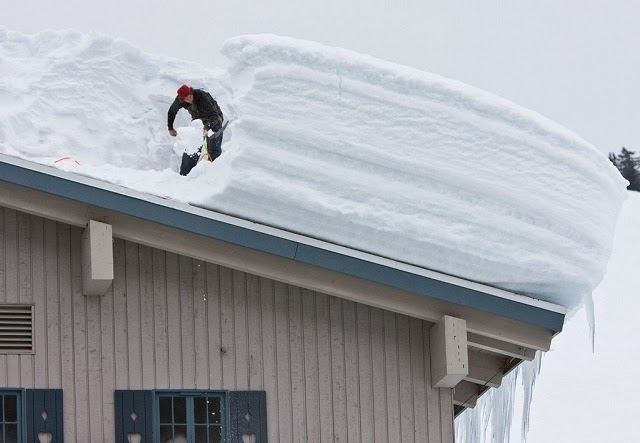 Photo of A man removing snow on the roof