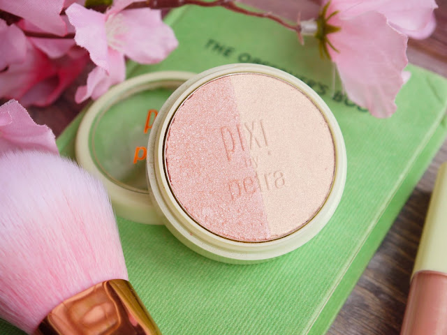 a round pale green pot containing blush split into two halves, one champagne, one peachy pink. The pot is sat on a green book with pink flowers and a pink makeup brush beside it.