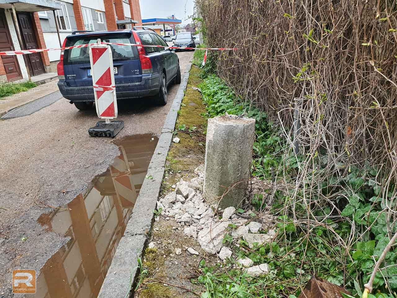 Daļēji nojauktais betona laternas stabs ielas malā
