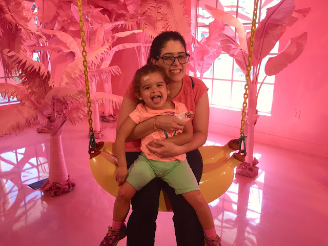 Mother and daughter seated on a swing shaped like a banana