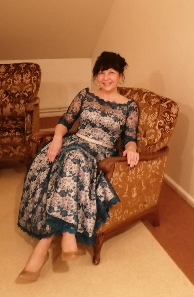Sieviete garā kleitā sēž uz krēslas