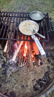 Rice cooking in a mess kit over a campfire