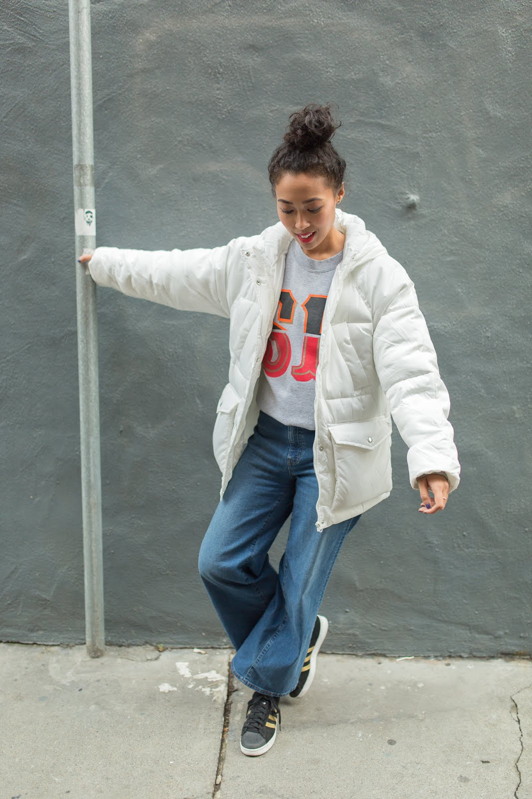 pancake stacker wearing a Booger Kids SF sweatshirt, Uniqlo wide leg jeans, Adidas Superstar shoes and ASOS white, puffer jacket.