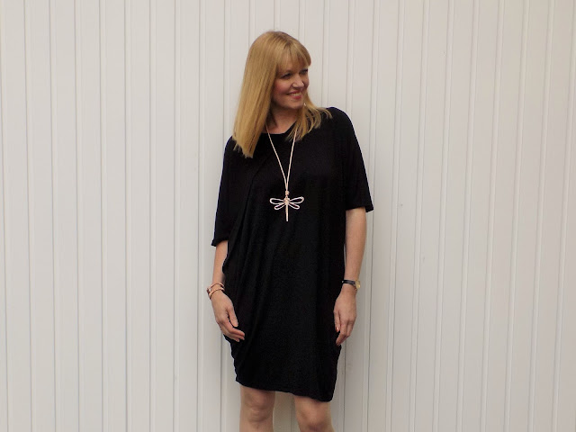 Black cocoon dress, rose-gold dragonfly pendant and colour block court shoes
