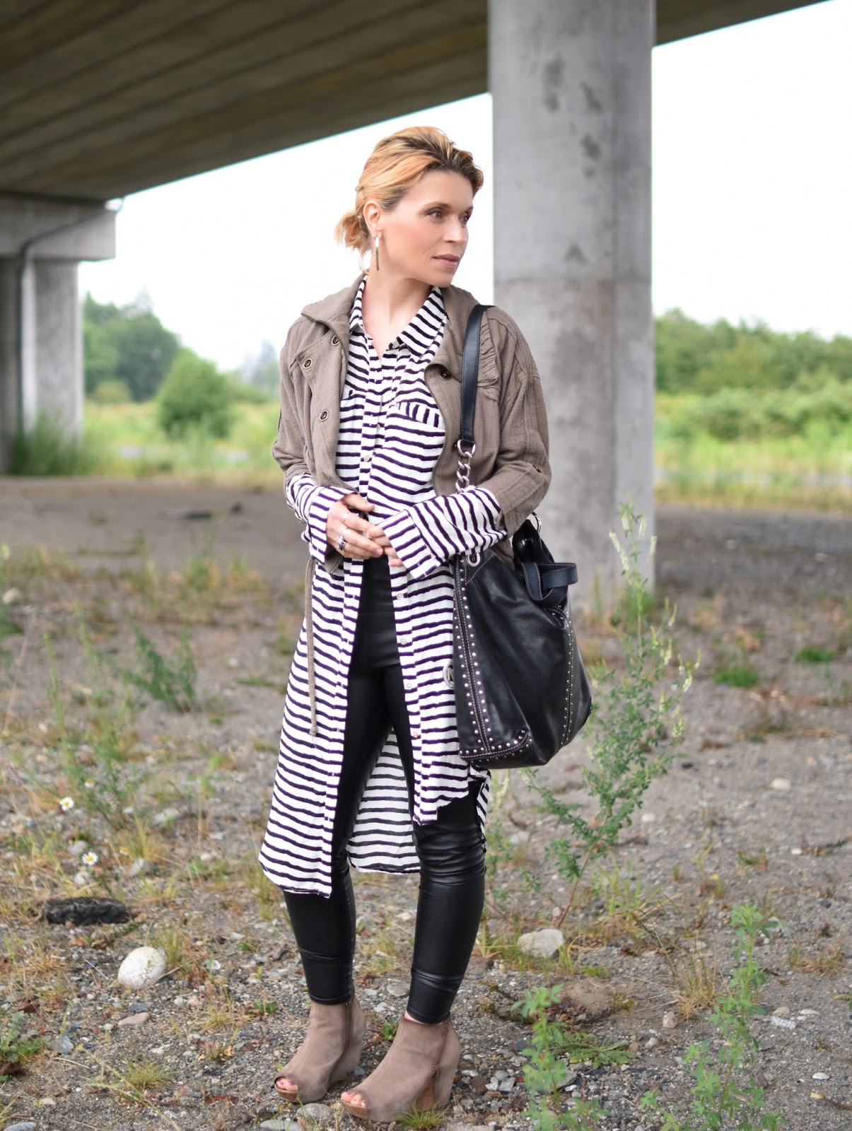 styling a striped shirtdress with vegan leather leggings, a bomber jacket, wedge heels, and an MK bag