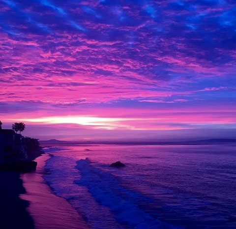 Image of a Californian sunset with a purple and red sky by the beach.