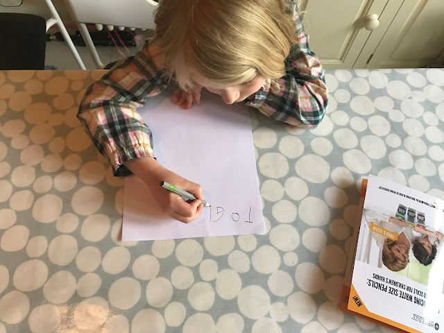 "M is sitting at the table writing a letter. SO far she has written ""To Gr"""
