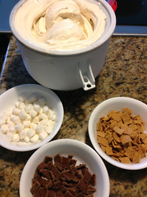 freshly churned ice cream next to bowls of marshmallows, grahams and chocolate