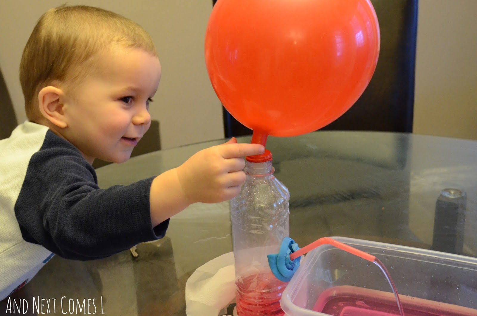 K checking out the balloon water fountain from And Next Comes L