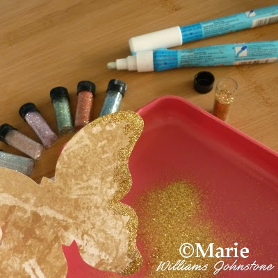 Adding glitter to the edges of paper butterflies spring summer craft