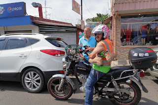 Man on motorcycle with small dog in Puriscal
