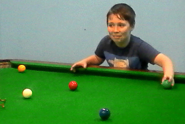 Boy holding a snooker ball.