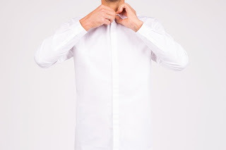 A man buttoning the final button in a white button-down