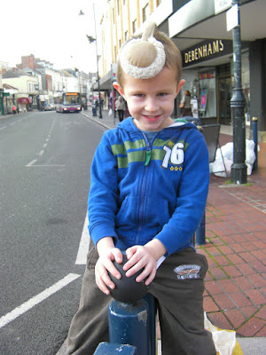 boy on railings in southsea with debenhams and earmuffs