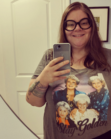 image of me standing in a mirror in my entryway, from the waist up, wearing large black-framed glasses and a grey t-shirt featuring the Golden Girls and text reading: Stay Golden