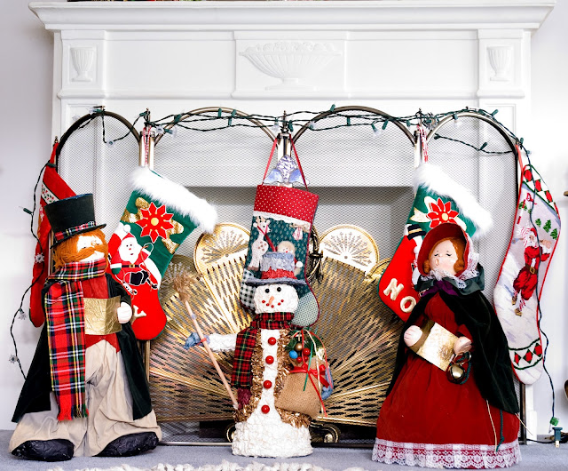 A plaster fireplace surround decorated for Christmas with vintage papier mache carolers and a papier mache snowman.