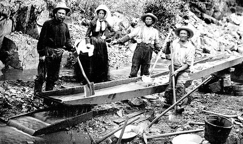 Image: 1850 Woman and Men in California Gold Rush | A woman with three men panning for gold during the California Gold Rush