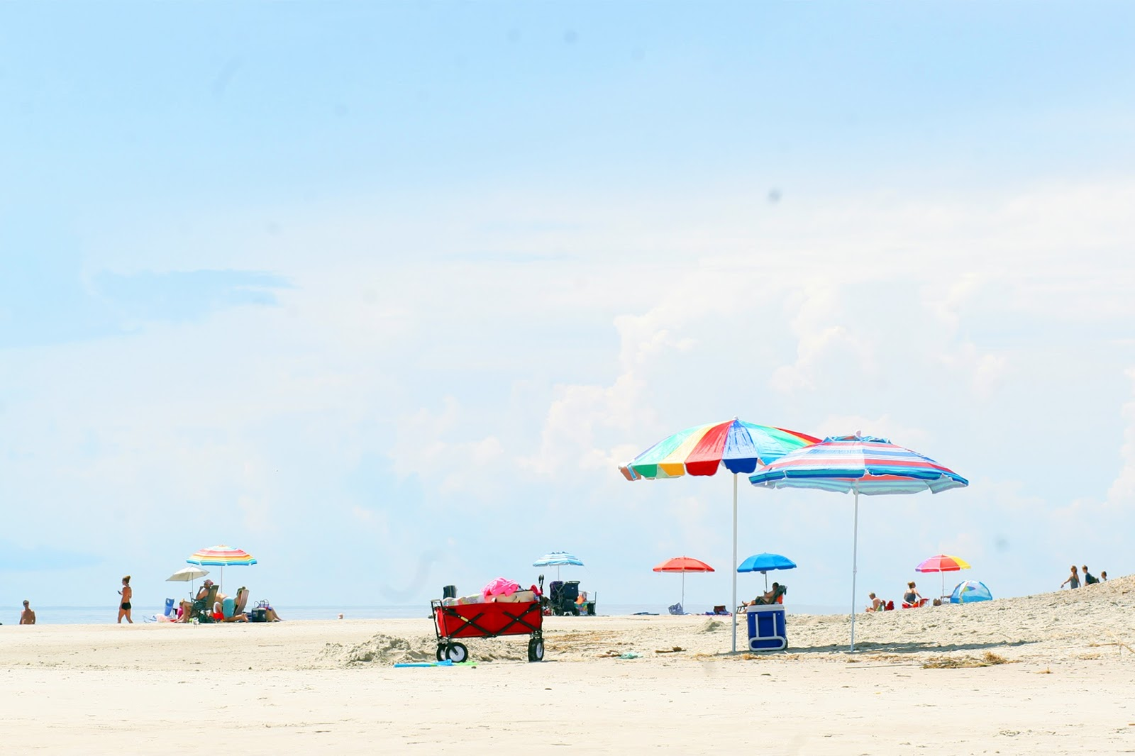 Colorful-beach-shot-of-rainbow-parasol-umbrellas-sunny-blue-sky-day