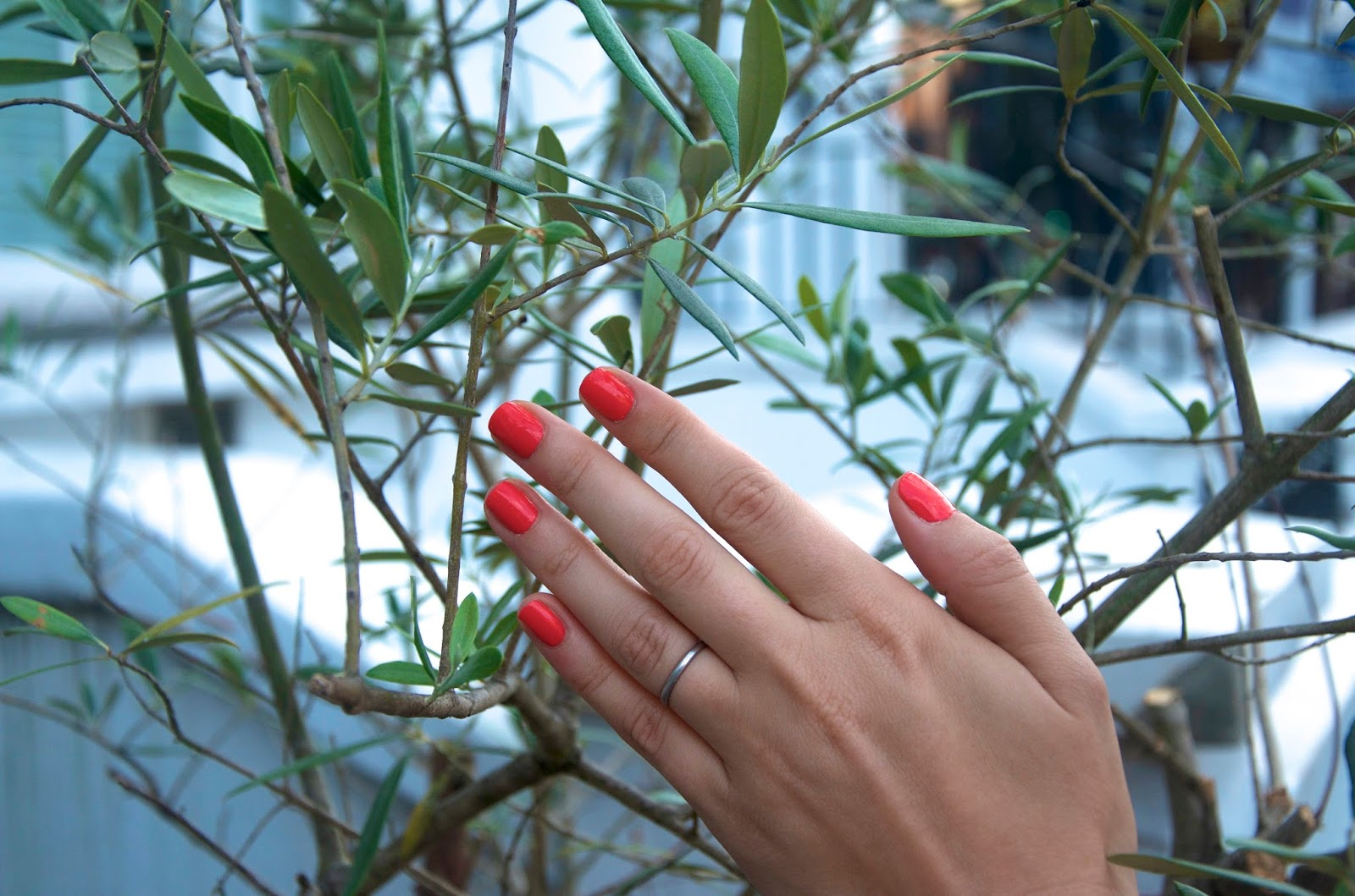 coral nails, platinum wedding band and greenery