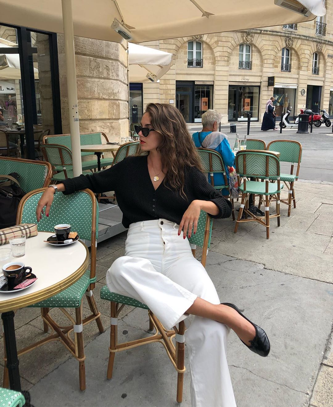 French-Girl Fall Outfit Idea With V-Neck Sweater, High-Waisted White Jeans, and Black Ballet Flats