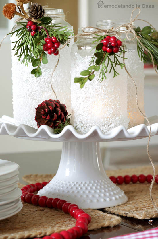Christmas table with white cake stand and mason jar luminaries