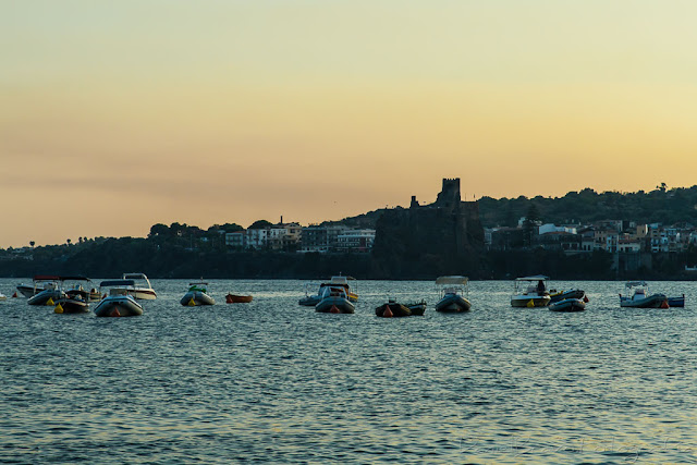 Vista desde Aci castello sobre el mar donde se ven pequeñas embarcaciones al atardecer