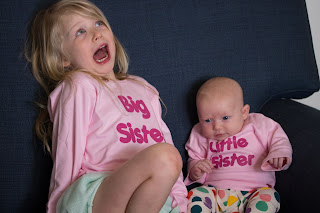 4 year old girl in pink big sister t shirt and 6 week old girl in pink little sister t shirt