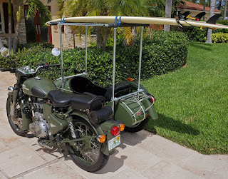 Motorcycle and sidecar with surfboard on top.