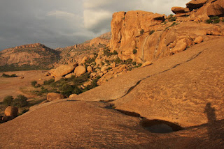 Геоглифы Намибия Южная Африка Очень сильная энергетика Намибийских сфер.  Меняет генный код. Силовое магнитное влияние на кристаллические структуры.   Геоглифы и места силы Намибии, потрясающее открытие.  Таинственные геоглифы в Намибии часть первая Круги в скалах  Как ясно из названия, в видео будет показана первая часть из трёх о неизученных геоглифах в Намибии, в самом сердце Южной части Африканского континента. Местность со скальными породами у поверхности, на вершине скал есть вырезанные или выплавленные неизвестным методом древние круглые выемки. Почти идеально круглые, до 5 метров в диаметре и до метра в глубину. Очень красивая местность и красочный пейзаж, можно увидеть крупные стоячие, балансирующие валуны размером с двухэтажный дом и весом около тысяча тонн. Эти камни округлённой формы без сомнения имеют природное происхождение. Но есть и некие загадочные следы обработки камня, которые не встречаются на других подобных скальных массивах в Намибии. Судя по всем внешним признакам им тысячи лет, древние люди, жившие в этом красотой наполненном месте, ощущали особую энергетику камней и сделали его культовым. В окрестностях можно найти множество красивых наскальных рисунков в небольших пещерах. Круглые каменные углубления наверняка не могли быть сделаны человеком и объяснить их природными процессами трудно, тем более, что более они нигде не повторяются. Это как петроглифы на камнях в Европе только в большем масштабе, вместо сложных символов, простые круги.