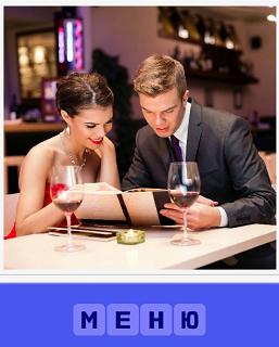 мужчина с женщиной в ресторане рассматривают меню и выбирают