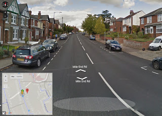 Mile End Road, Colchester, looking northwards. Wide road with cars parked beside each kerb.