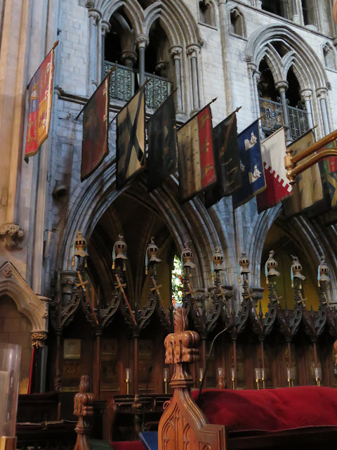 Crests, helmuts, and swords lined up at the front of St. Patrick's Cathedral in Dublin