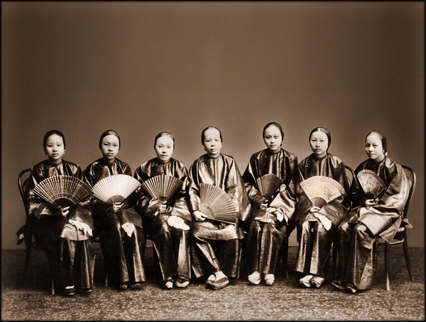 Superstições chinesas - sete mulheres sentadas com roupas tradicionais e leques chineses
