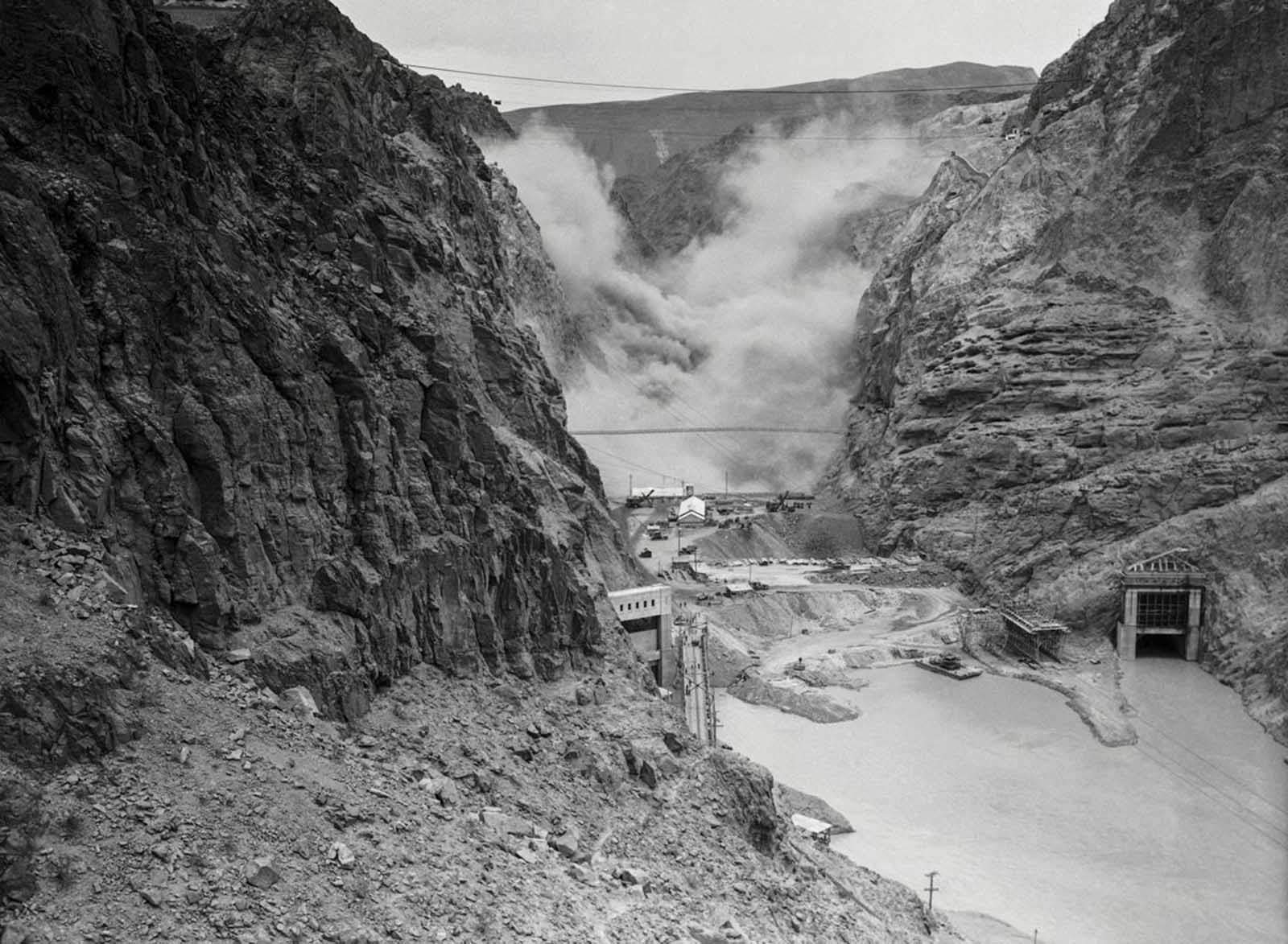 Four tons of dynamite are detonated in the canyon in the early stages of construction. May 12, 1933.