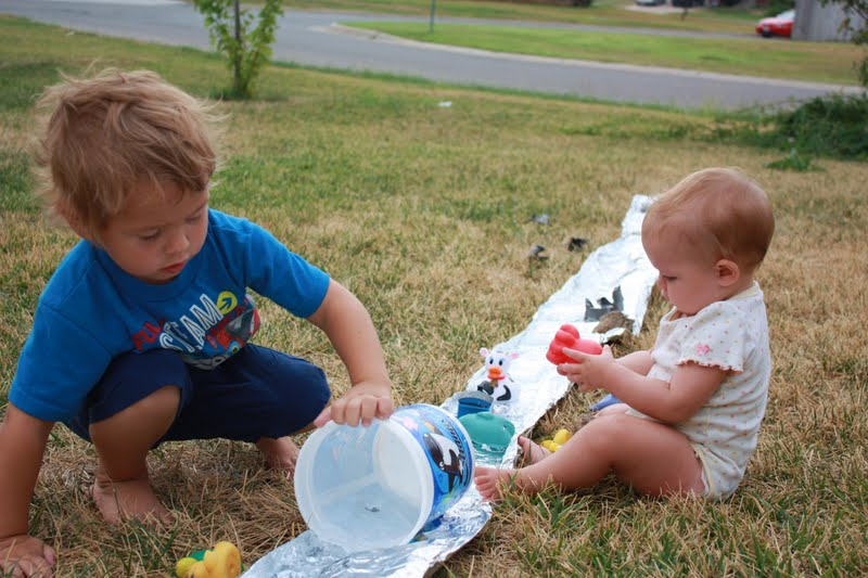 Kids playing with a foil river outdoors