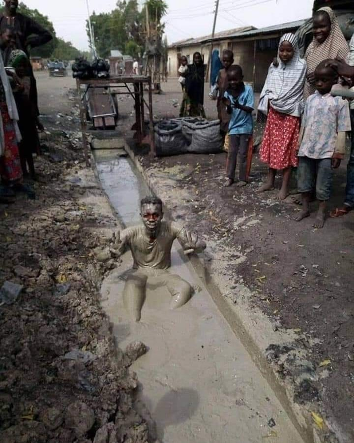 A man celebrates Buhari victory by swimming in Dirty Water
