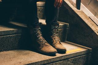 botas de amarrar cafés sobre peldaño de escalera