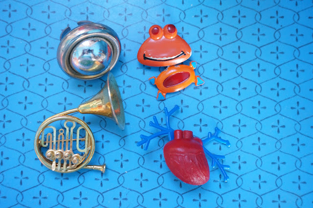 une bague de pacotille , une sorte de Casimir en broche   ... et ça continue un cor et un coeur , ce n'est que le début ...  space age ring , orange monster brooch , french horn brooch , heart brooch