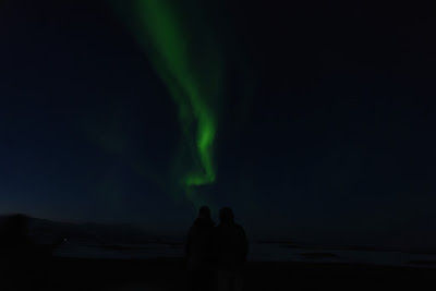 Pareja viendo juntos la aurora boreal, uno de los planes más románticos en Islandia
