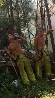 Foto(uma das fotos do calendário 2017 Austrália). Dois bombeiros desnudos da cintura para cima em meio a selva com muita fumaça branca; usam calças verdes de tecido grosso com bolsos chapados na altura das coxas, listras duplas em verde-limão nas laterais e na altura dos tornozelos, cinto com tiras largas de segurança em preto e vermelho. Eles têm porte atlético, sarados, músculos fortes e abdomens definidos. Estão em pé, lado a lado, um, à esquerda, apoia o bumbum e o antebraço direito em um pequeno barco abandonado cheio de folhas secas dentro, com a mão esquerda segura uma garrafa de água próximo a boca, com a cabeça inclinada para trás, bebe sem encostar o gargalo; o outro, apoia o antebraço esquerdo em um fino e alto tronco enquanto observa o colega hidratando-se. Próximo a eles, há instrumentos e acessórios de combate ao fogo.