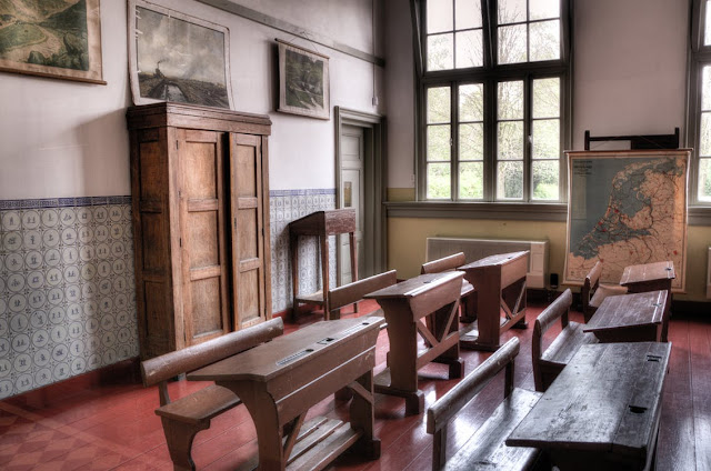 Escuela antigua con bancos de madera y mapa.
