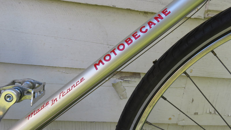 Silver bicycle frame with red lettering.