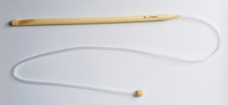 A bamboo tricot hook with a cable attached. The hook is resting horizontally across the top half of the picture with a clear plastic tubing attached to the end instead of a stopper. The plastic tubing bends to fill the bottom half of the picture and has a stopper at the end of the tubing.