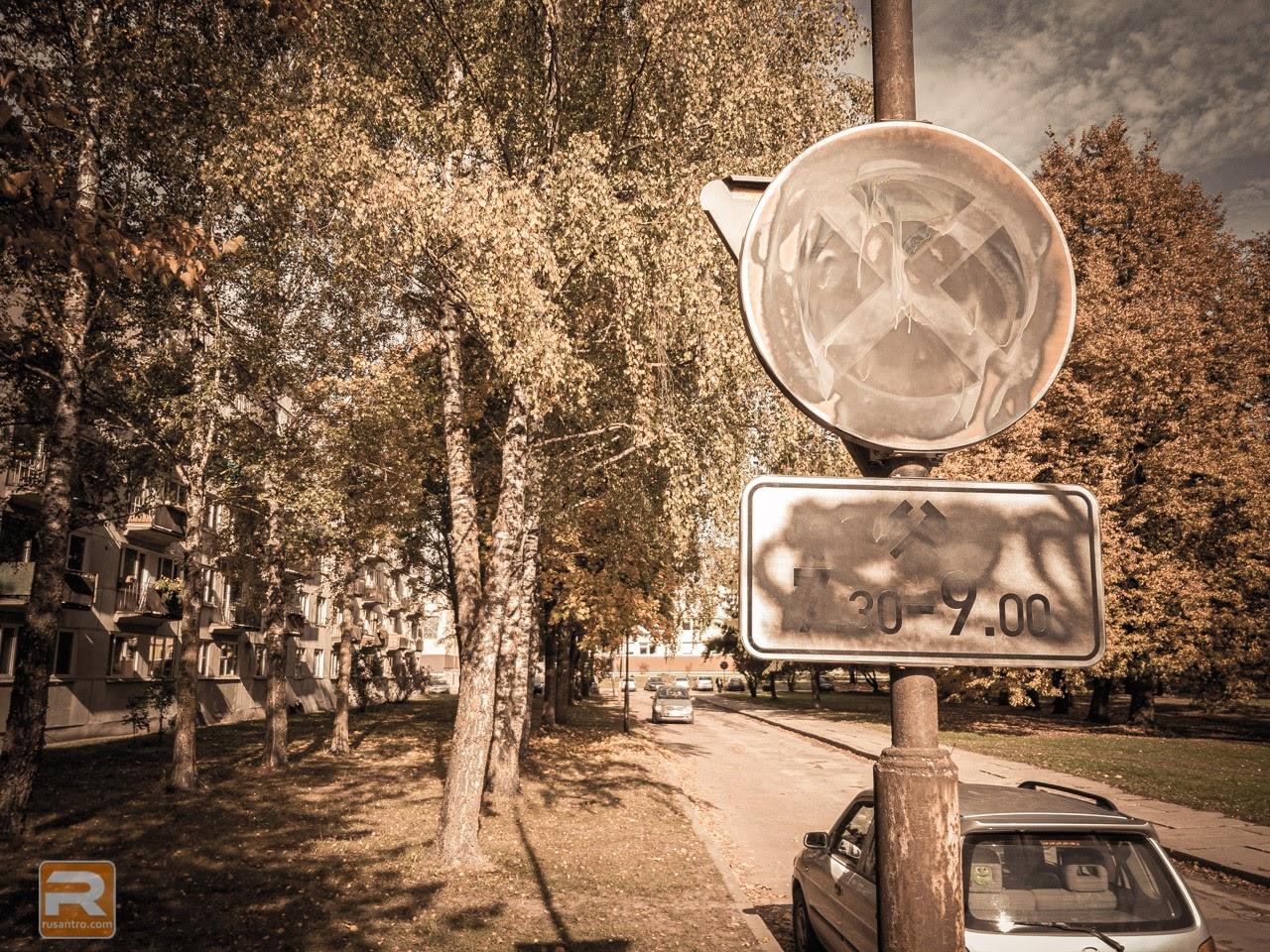 Ar krāsu aizkrāsota ceļa zīme uz rudenīgu koku fona