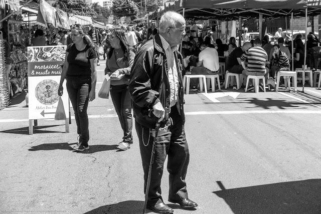 Pessoas na feira com um senhor com bengala no primeiro plano
