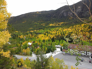 Fall scene above and around a small mountain town with Aspen trees turning golden and yellow colors.