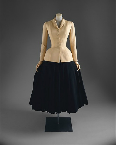 Beige form fitting jacket with black full skirt in Dior New Look style on display on dress form