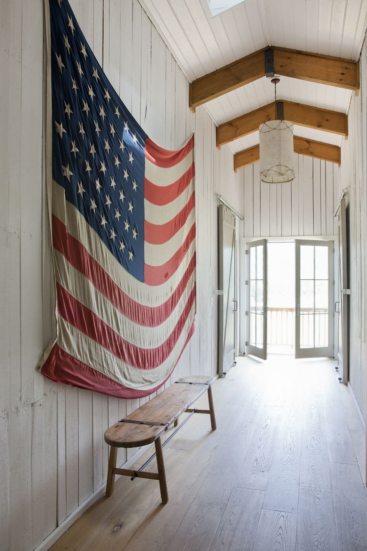 A Large American Flag In White Washed Cottage Hallway With Wide Planked Floors And An Interesting Driftwood Like Bench Doors Thrown Open To The Sand