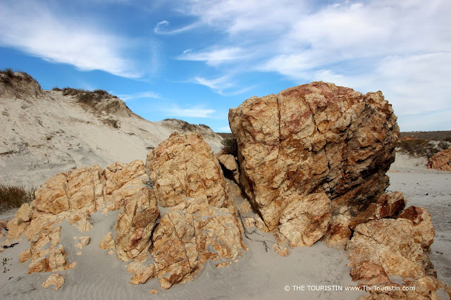 Rock formations on a white sand beach with high dunes in the background under a light blue and cloudy sky.